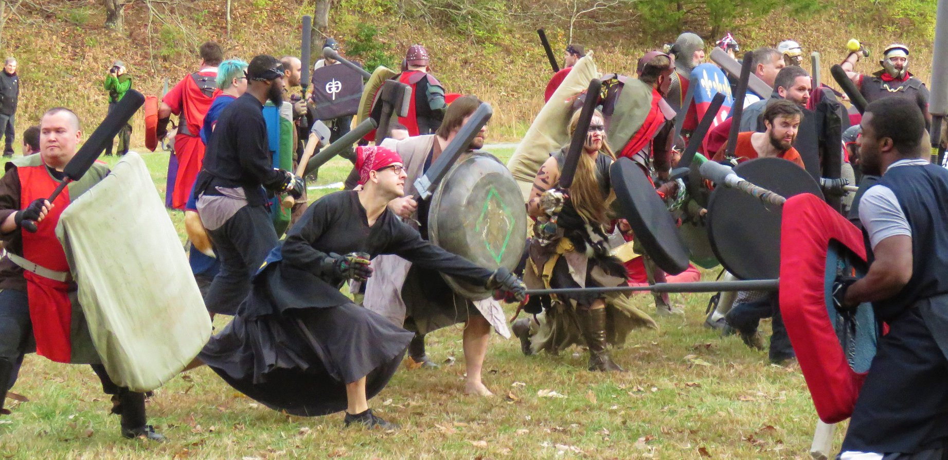 Two armies fighting each other. Multiple individual fighters swinging weapons on both sides.